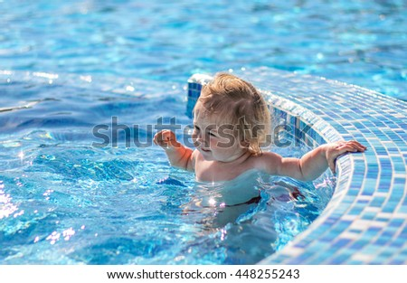 Happy baby girl playing in pool on a hot summer day during vacation