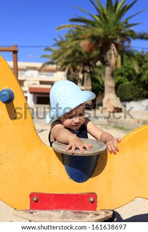 Happy Baby Girl playing in swing in the playground