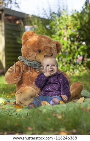happy baby girl playing outside at the garden with her teddy bear.