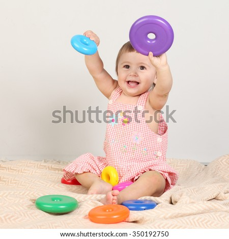 Happy baby girl playing with colorful toy