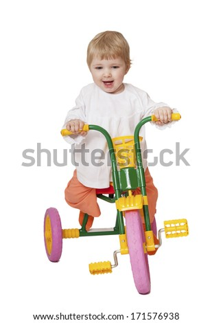 Happy baby girl rides tricycle - stock photo