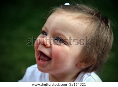 Happy baby girl sitting in sunshine - stock photo