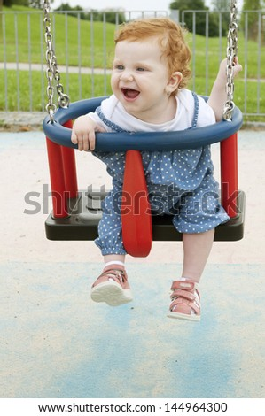 Happy Baby Girl Sitting in the Swing - stock photo