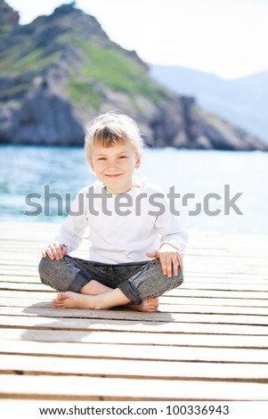 Happy baby girl sitting on berth in summer