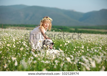 Happy baby girl stroking her dog in camomile field - stock photo