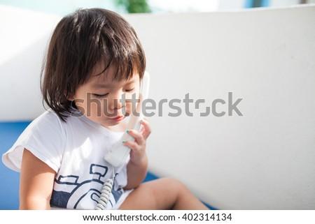 Happy baby girl talking on phone  - stock photo