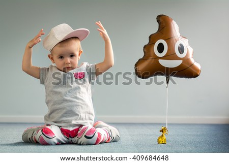 happy baby girl toddler plays in room with toy hat funny smile laugh blue carpet balloon poo emoji emoticon   - stock photo