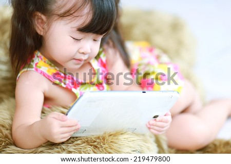 Happy baby girl using tablet computer - stock photo