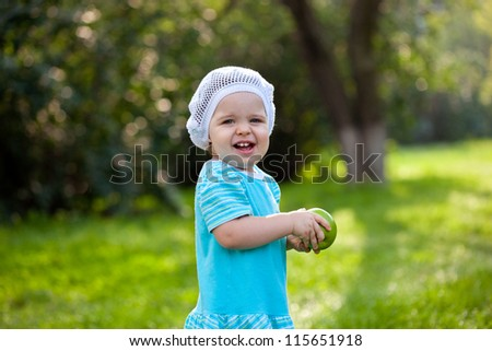happy baby girl wearing blue dress walking in the park and holding green apple