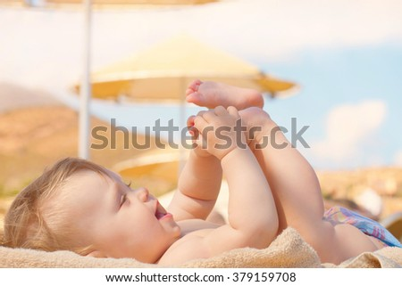 Happy baby having fun and sunbathing on the beach sunbed.