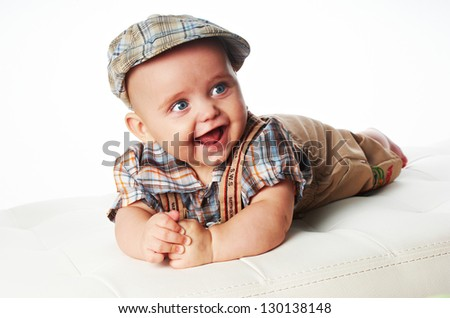 Happy baby in a cap lying on the couch