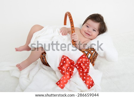 happy baby in basket on white towel - stock photo