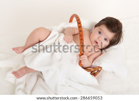 happy baby in basket on white towel