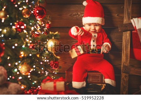 Happy baby in costume Santa Claus with gift  at christmas tree
