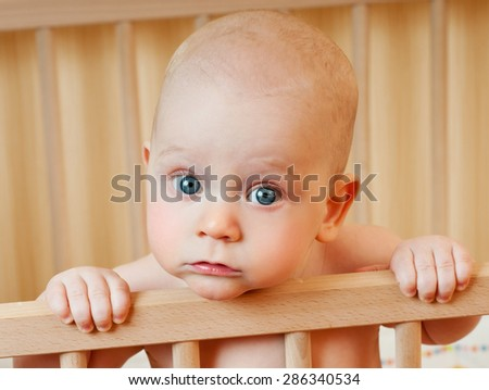 Happy baby in her crib. - stock photo