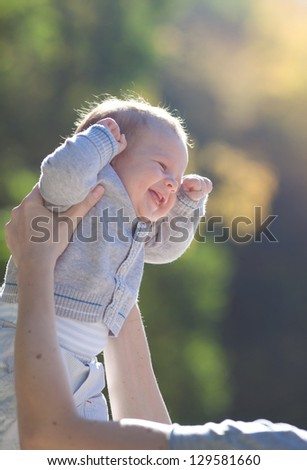 happy baby in mother hands, outdoor - stock photo