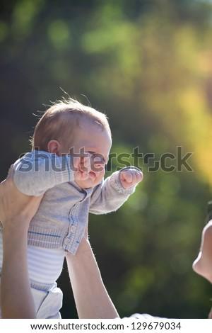 happy baby in mother hands, outdoor - stock photo