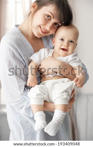 Happy baby in mother's arms in her room - stock photo