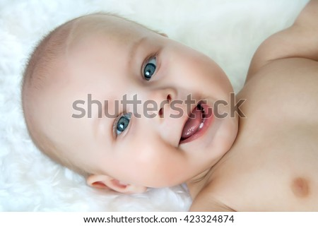 Happy baby infant with first tooth  lying on texture blanket close-up portrait. Looking at camera. - stock photo