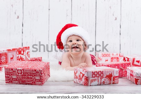 happy baby laying  among the christmas gifts