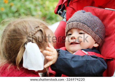 Happy baby looking with love and touching a cheek of his elder sister, outdoor portrait - stock photo