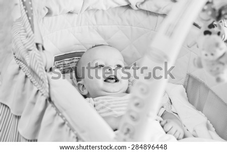 Happy baby lying in the cradle and looking at toys  (black and white) - stock photo
