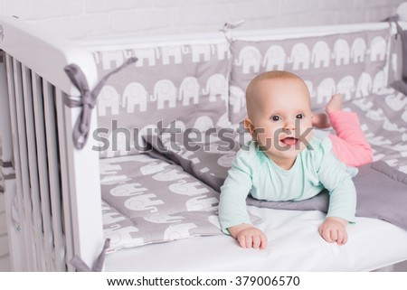 Happy baby lying on his stomach in cot. Child lying in a bed. Happy childhood. - stock photo