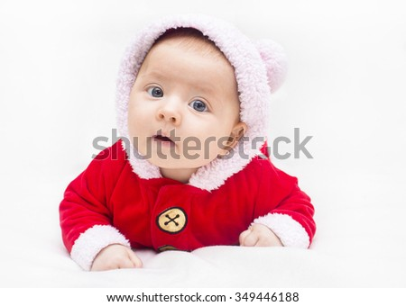 Happy baby lying on tummy wearing a red and white Christmas Santa suit, indoor shot