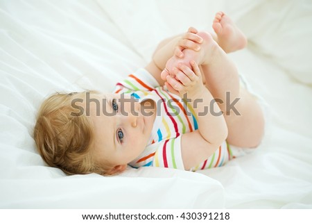 happy baby lying on white sheet and holding his legs - stock photo