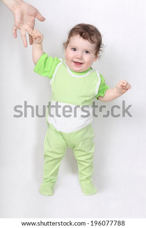 Happy baby making first steps holding father hand - stock photo