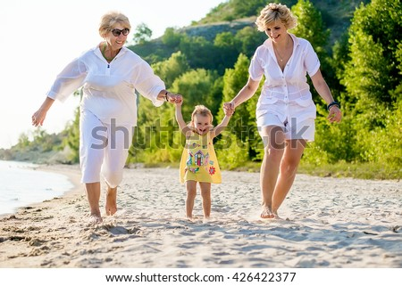 Happy baby, mother and grandmother together. baby, mother and grandmother with a walk on the beach in summer