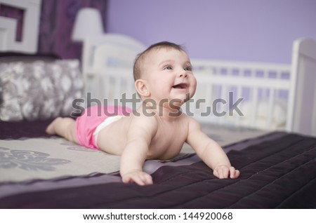 Happy baby on a bed, lying and smiling. Cradle is in the background.
