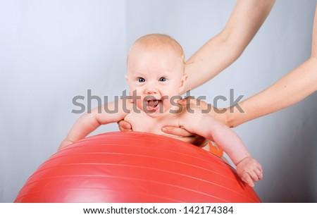 Happy baby on gymnastic ball - stock photo