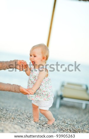 Happy baby on the beach trying to start walking with mothers help