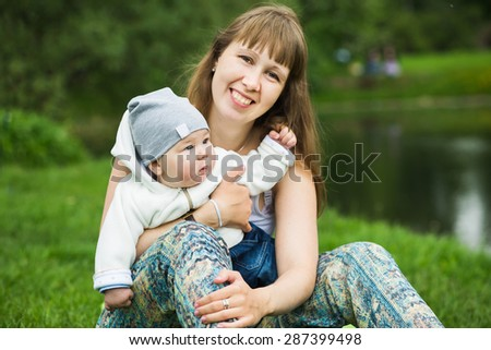 Happy baby on the mother's hands in the summer park