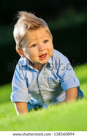 happy baby playing on green grass in spring park - stock photo