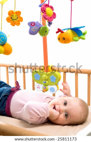 Happy baby playing with bed side toy, smiling, isolated on white background.