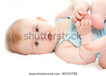 happy baby playing with his feet, on white background - stock photo