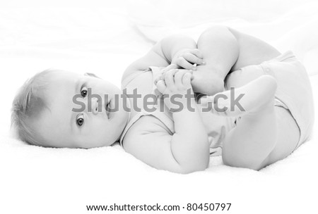 happy baby playing with his feet, on white background