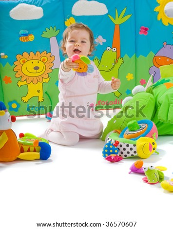 Happy baby playing with soft toys, smiling, isolated on white background.