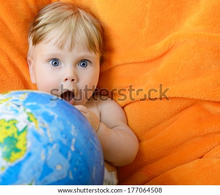 Happy baby playing with terrestrial globe on an orange plaid - stock photo