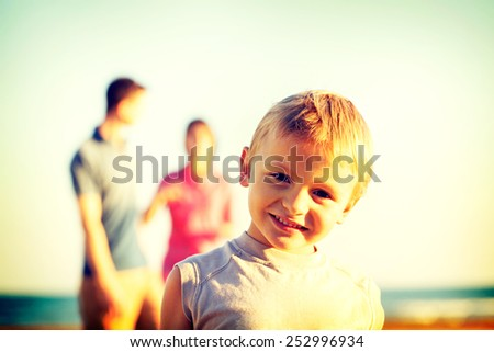 happy baby posing for a photo at the sea while parents look at him - stock photo