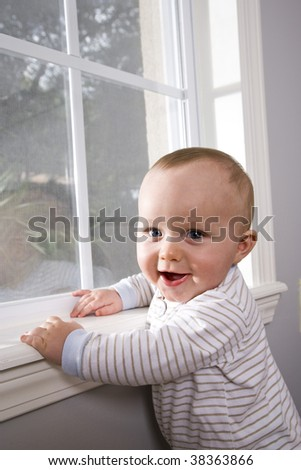 Happy baby pulling himself up on window sill