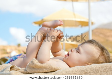 Happy baby resting on the beach sunbed. 8 month old kid lying on sun lounger and playing with her feet. Summer holidays concept. - stock photo