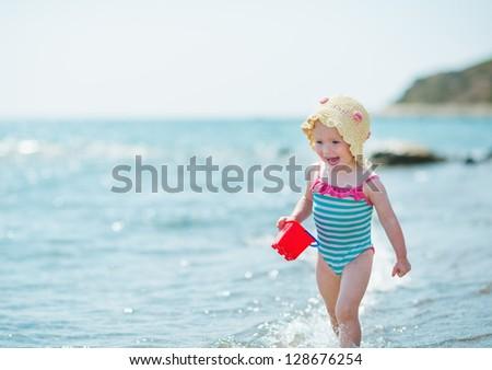 Happy baby running along sea shore - stock photo