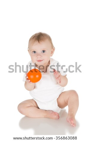 happy baby sitting and playing with small ball toys over white background, motor skill development; front view; white clothes