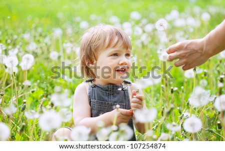 happy baby sitting in dandelion meadow