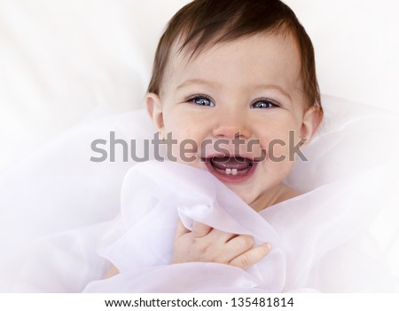 happy baby sitting in her chair wearing white - stock photo