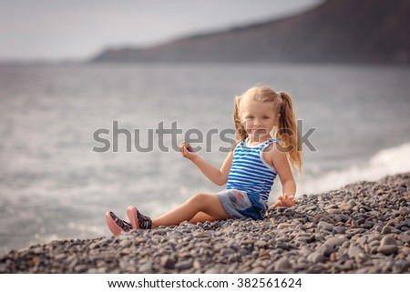 happy baby sitting on the beach