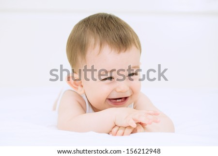 Happy baby smiling and resting on the bed - stock photo